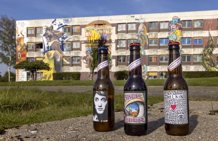 Photo de 3 bières devant un mur décoré d'une fresque